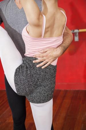male ballet dancer: Midsection of male trainer helping female ballet dancer in performing split at studio