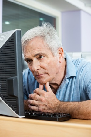 tensed: Tensed senior man looking at computer monitor while sitting in class