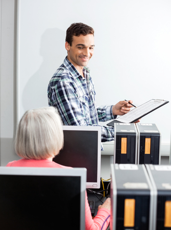 the elderly tutor: Happy young tutor holding clipboard at whiteboard with senior female student in computer class