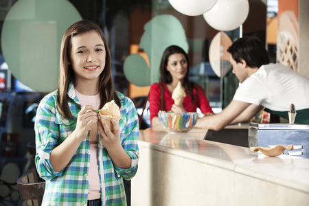 gelati: Portrait of smiling girl having ice cream while mother and waiter standing at counter in parlor