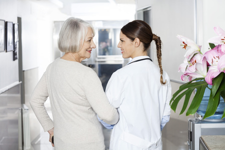 long term care services: Rear view of disabled senior woman standing arm in arm with female doctor at rehab center