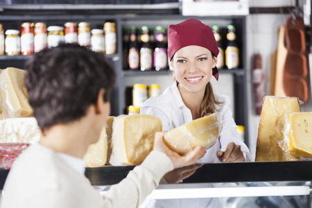 Smiling young saleswoman selling cheese to man in grocery store Stock Photo