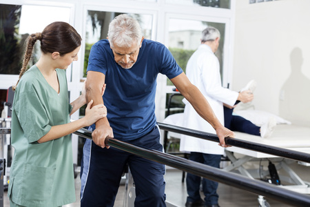 Female physiotherapist standing by senior patient walking between parallel bars in rehabilitation center Foto de archivo
