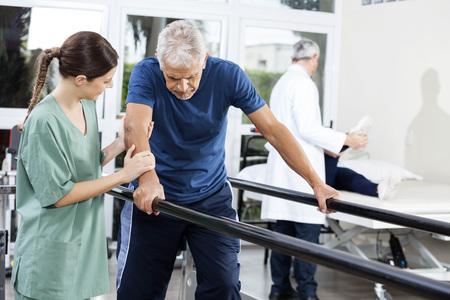 Female physiotherapist standing by senior patient walking between parallel bars in rehabilitation center Standard-Bild