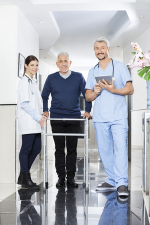 long term care services: Full length portrait of physiotherapists and senior male patient standing in rehab center