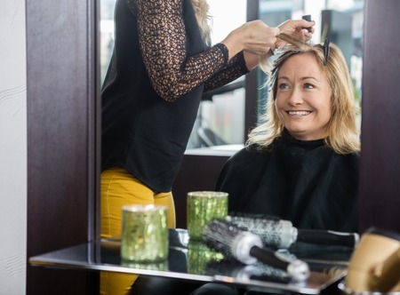 hairtician: Smiling mature woman getting her new hairstyle in beauty parlor
