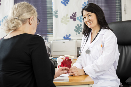 middle joint: Smiling orthopedic doctor looking at female patient at desk in clinic