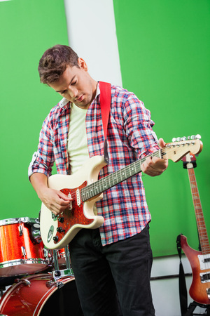 down beat: Handsome male guitarist performing in recording studio Stock Photo