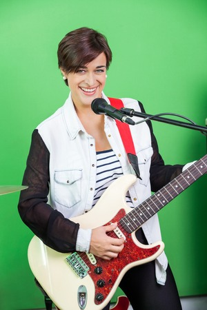 signer: Portrait of happy female signer playing guitar while singing in recording studio