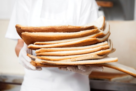midsection: Midsection of female baker holding bread waste in bakery