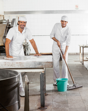 Portrait of confident male Baker's in uniform cleaning bakery Stock Photo