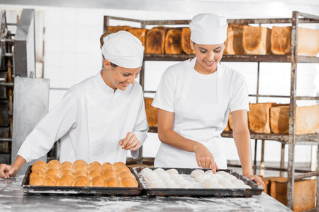 panino: Happy female Bakers analyzing dough at table in bakery Stock Photo
