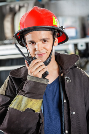 walkie talkie: Portrait of confident male firefighter using walkie talkie at fire station