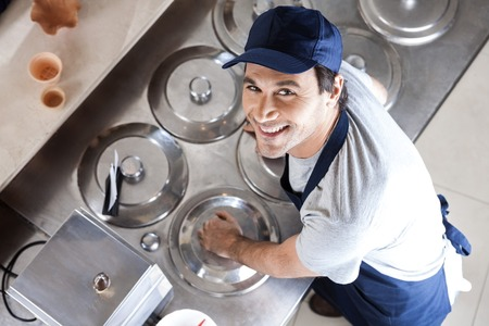 lids: High angle portrait of waiter leaning on lids at counter in parlor Stock Photo