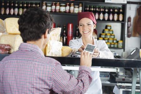 saleswoman: Smiling saleswoman accepting payment from male customer in cheese shop