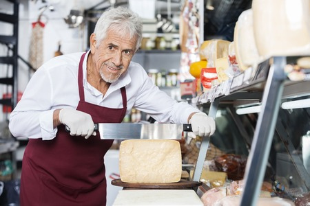 handled: Portrait of happy salesman slicing cheese with double handled knife at counter in shop