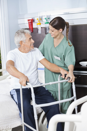 long term care services: Smiling senior man being assisted by female nurse in using Zimmer frame at rehab center