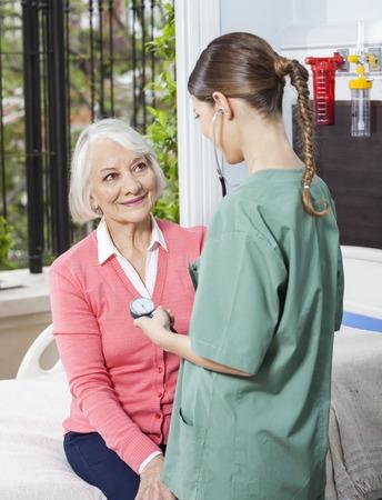 eldercare: Female nurse examining blood pressure of senior patient in rehabilitation center