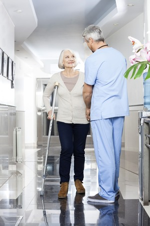 long term care services: Mature physiotherapist helping senior patient with crutches in rehab center