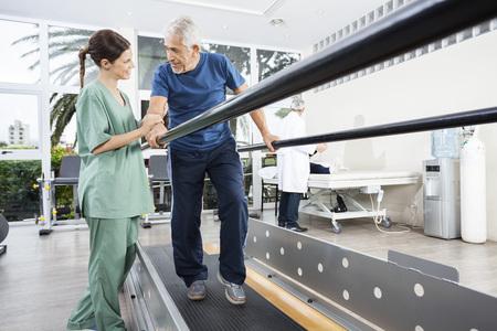 Żeński physiotherapist patrzeje starszego cierpliwego odprowadzenie między równoległymi barami w rehab centrum