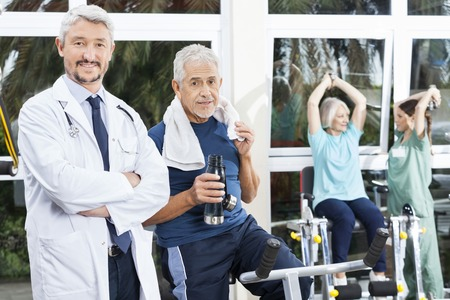 rehab: Portrait of confident senior man and doctor in fitness studio of rehab center