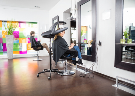 Male and female customers undergoing hair treatment in parlor