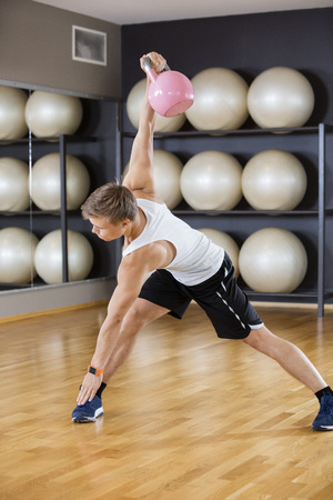 touching toes: Full length of young man exercising while lifting kettlebell on hardwood floor at gym