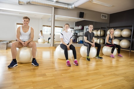 ropa deportiva: Full length portrait of male and female friends sitting on exercise ball at gym