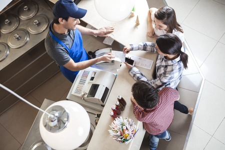 gelati: High angle view of waiter giving receipt to female customer standing with family at icecream parlor