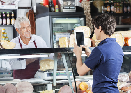 telephone salesman: Young man photographing salesman packing cheese in shop Stock Photo