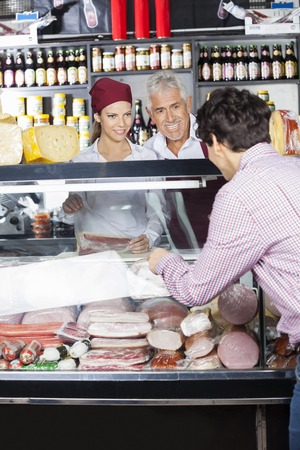salespeople: Salespeople assisting male customer in buying cheese at shop Stock Photo