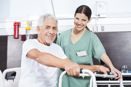 long term care services: Portrait of female nurse and senior male patient with walker at rehab center Stock Photo