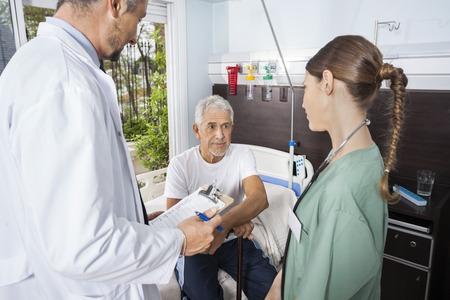 Senior patiënt op zoek naar vrouwelijke verpleegkundige terwijl dokter rapporten in rehab centrum Stockfoto