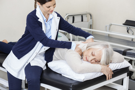 rehab: Female physiotherapist giving massage to senior woman in rehab center