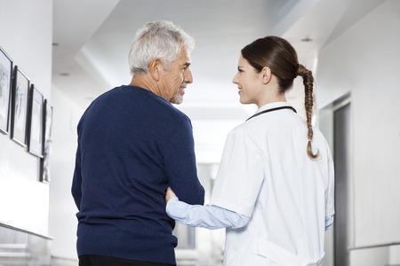 Achter mening van vrouwelijke arts die arm senior man in revalidatiecentrum
