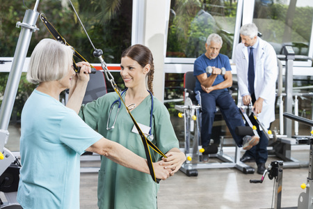 Happy female nurse assisting senior woman with resistance band exercise in rehab fitness center