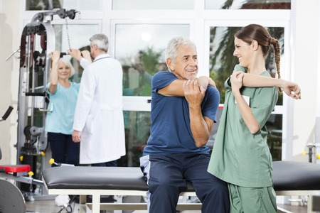 guiding: Smiling female nurse guiding senior patient in arm exercise at rehab fitness center