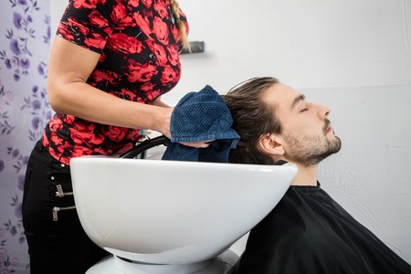 mid adult   female: Mid adult female hairdresser wiping male customers hair in salon