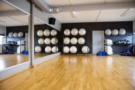 Pilate balls arranged in shelves by mirror at gym Stockfoto