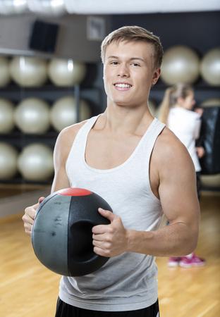 Portrait des jungen Mannes lächelnd in die Turnhalle Medizin Ball halten