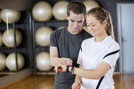 fitness gym: Fit young woman showing pedometer to male friend while standing in gym