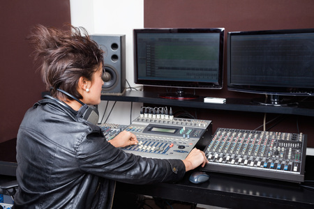 hair band: Rear view of young woman mixing audio in recording studio