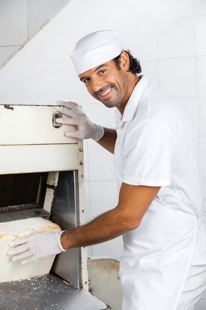 mid adult male: Portrait of smiling mid adult male baker using bread slicer at bakery