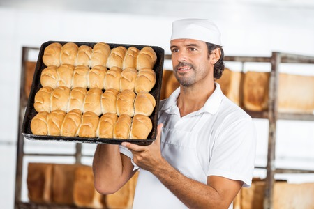 mid adult male: Mid adult male baker showing breads in baking tray while looking away at bakery Stock Photo