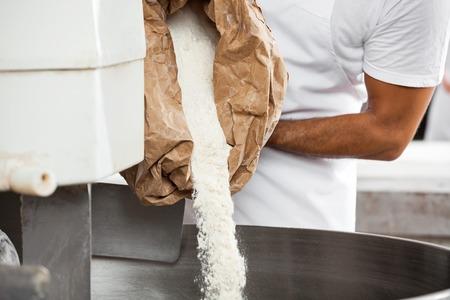 Midsection mi boulanger adulte verser la farine en pétrissant la machine à la boulangerie