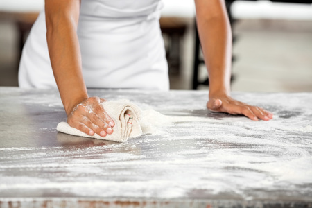 Midsection of female baker cleaning flour from table in bakery