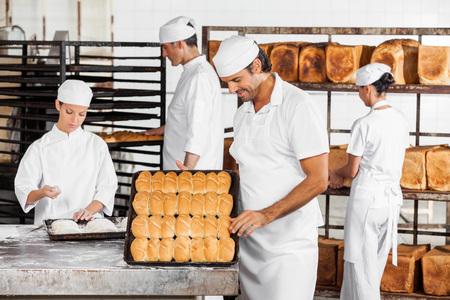 Metà uomo adulto analizzare pane mentre i colleghi che lavorano in panetteria photo