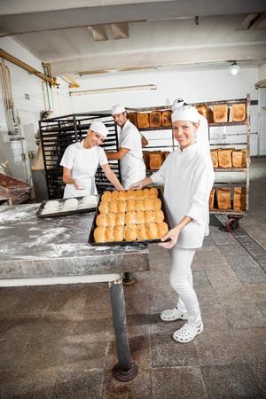 Ritratto di felice panettiere femminile che mostra pane cotto mentre i colleghi che lavorano in panetteria photo