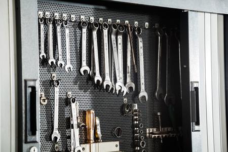 herramientas de mecánica: Diversas herramientas de trabajo que cuelgan en la pared en la tienda de reparación de automóviles Foto de archivo