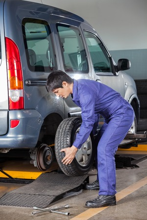replacing: Young male technician replacing car tire at auto repair shop